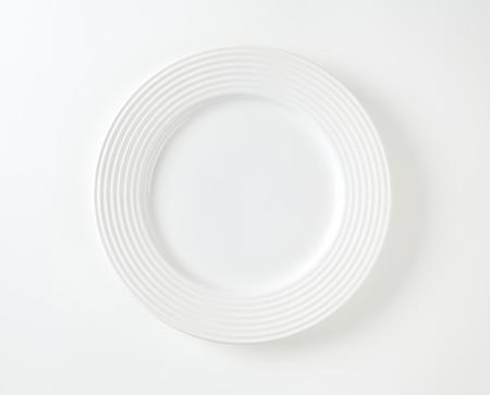 Witte porseleinen plaat met reliëf ringen op de velg
