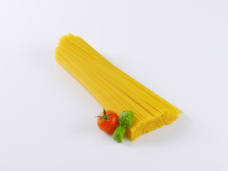 uncooked spaghetti, tomato and basil
