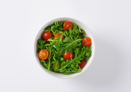halved  half: bowl of fresh rocket leaves with cherry tomatoes