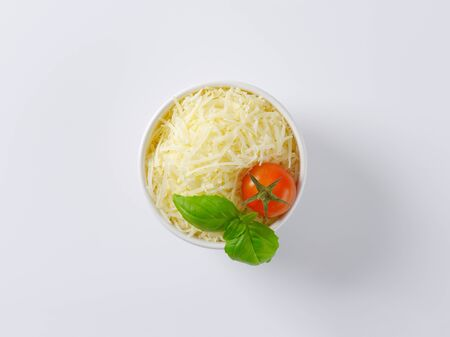 grated parmesan cheese: bowl of grated parmesan cheese, tomato and basil Stock Photo