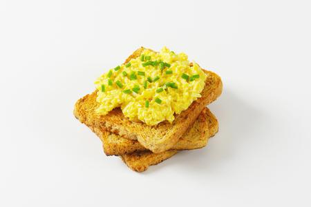 huevos revueltos: huevos revueltos con cebollino picado sobre una tostada