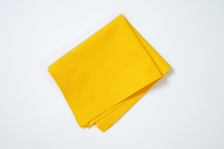 napkin: folded yellow cloth place mat