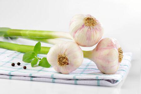 checked: three fresh garlic bulbs on checked tea towel