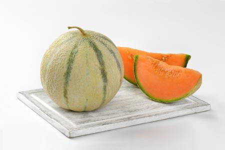 cantaloupe: fresh cantaloupe melon on wooden cutting board