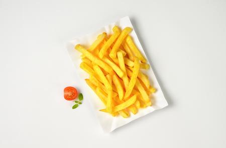 gedeelte van de Franse frietjes op papier plaat Stockfoto