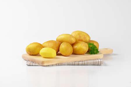 unpeeled: fresh unpeeled potatoes on wooden cutting board Stock Photo