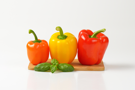 bell peppers: three bell peppers on wooden cutting board Stock Photo