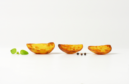 accompaniment: three potato wedges on white background