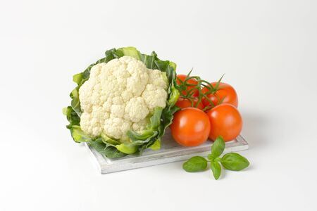 head of cauliflower: head of fresh cauliflower and tomatoes on wooden cutting board