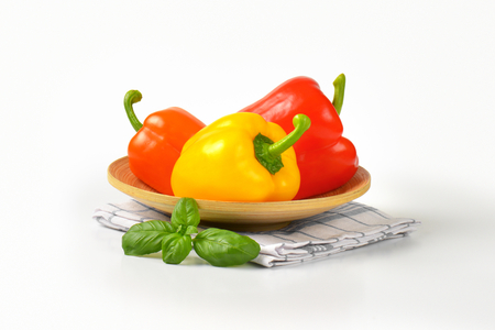 bell peppers: three ripe bell peppers on bamboo plate