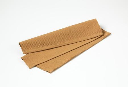 place mat: Folded brown woven cotton place mat
