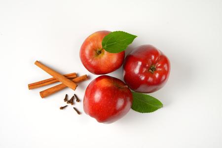 apfel: drei rote Äpfel, Zimtstangen und Gewürznelken auf weißem Hintergrund