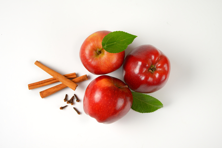 above view: three red apples, cinnamon sticks and dried cloves on white background Stock Photo