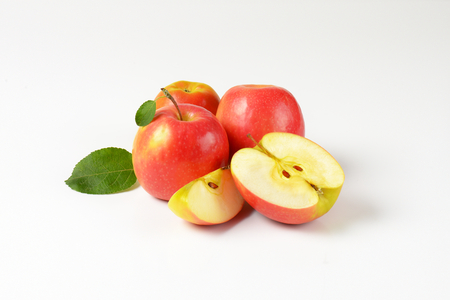 halved  half: whole and cut apples with leaves on white background