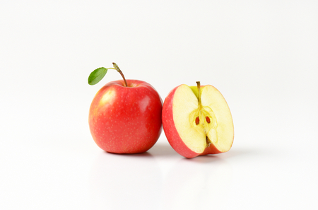 halved  half: one and a half red apples on white background Stock Photo