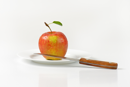 white washed: washed red apple and kitchen knife on white plate