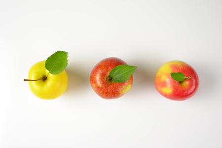 drie rijpe appels in een rij op een witte achtergrond Stockfoto