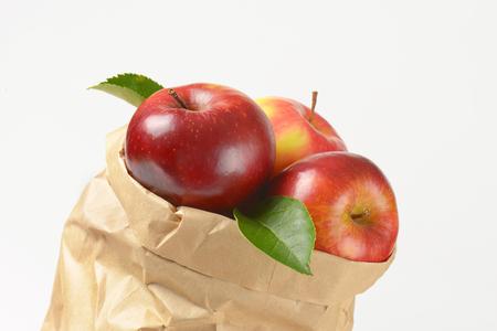 apple paper bag: close up of ripe apples in paper bag