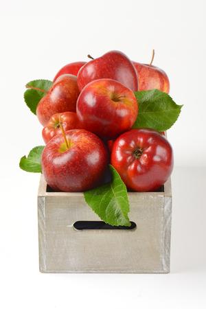 caja de manzanas rojas sobre fondo blanco