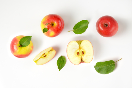 whole and cut apples with leaves on white background