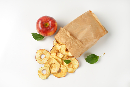 apple paper bag: fresh red apple and dried apple rings coming out of paper bag