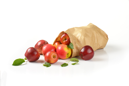 apple paper bag: fresh red apples spilling out of a paper bag