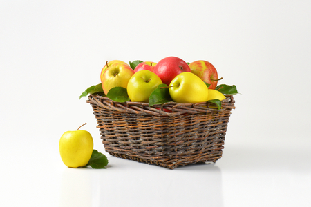 basketful: red and yellow apples in wicker basket Stock Photo
