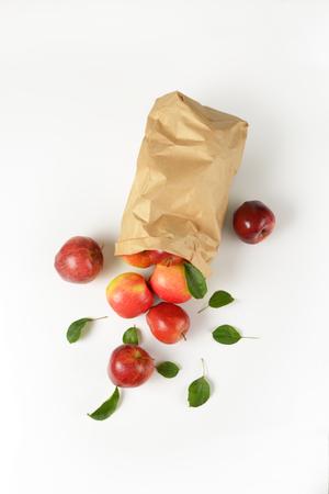 manzana roja: manzanas rojas frescas se derraman fuera de una bolsa de papel