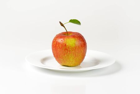 washed: washed red apple with leaf on white plate