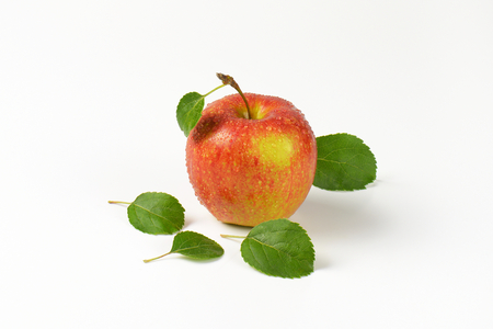white washed: washed red apple with leaves on white background
