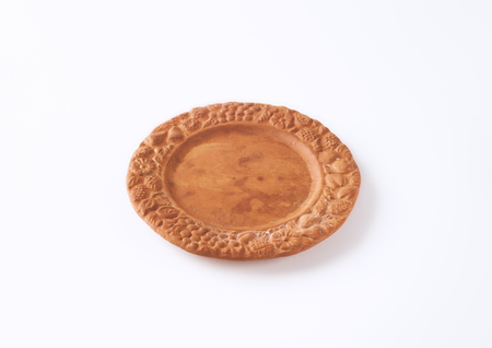 antique dishes: rustic clay plate with decorative rim