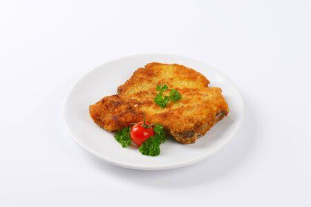breaded: fried breaded pork chop on white plate