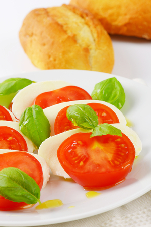 french bread rolls: plate of caprese salad and fresh buns Stock Photo