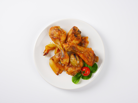 roasted chicken: freshly roasted chicken legs and vegetables on white plate