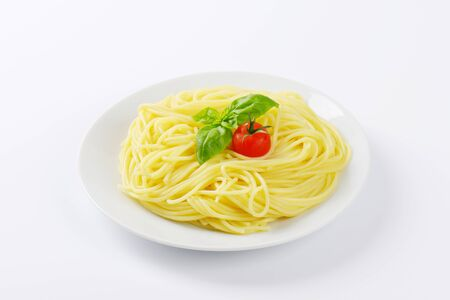 long shots: heap of boiled spaghetti, basil and cherry tomato on white plate
