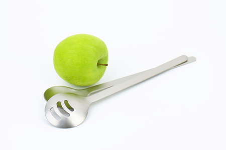 serving utensil: metal salad spoon and fork and green apple