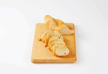 crusty french bread: sliced loaf of French bread on cutting board