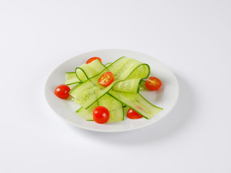 halved: thin slices of fresh cucumber with halved cherry tomatoes