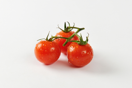 Three wet cherry tomatoes on vine