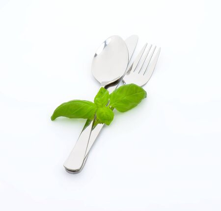 knife, fork and spoon and fresh basil leaves Stock Photo