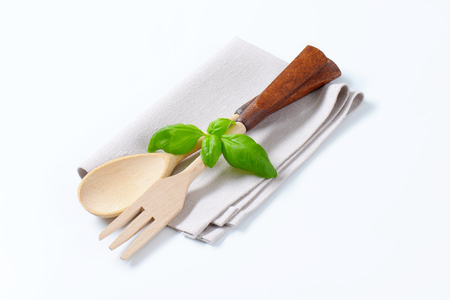 serving utensil: wooden fork and spoon with fresh basil on napkin Stock Photo