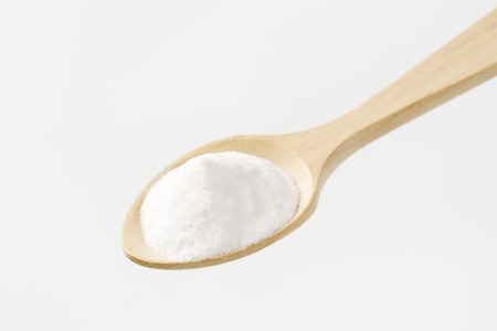 sodium bicarbonate: heap of cooking soda on wooden spoon