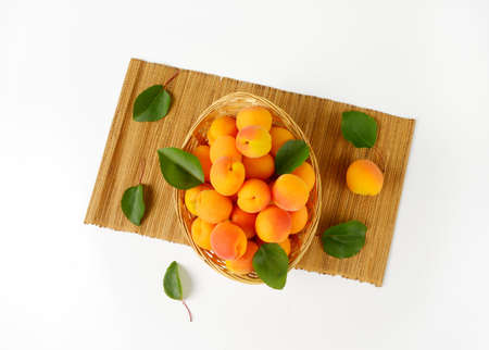 fruits in a basket: Fresh apricots in basket bowl