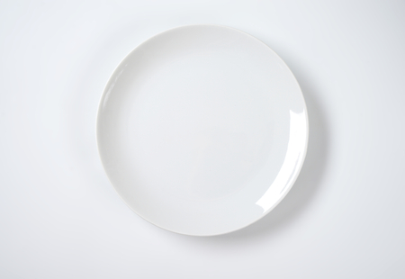 rimless: empty rimless white plate on off-white background Stock Photo