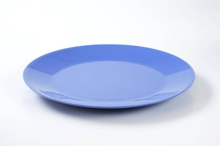 rimless: empty blue dinner plate on off-white background Stock Photo