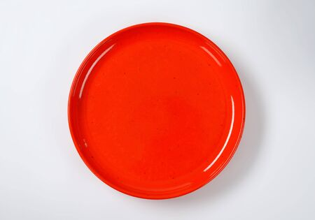 rimless: empty round red dinner plate
