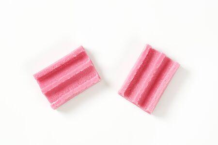 goma de mascar: dos piezas de goma de mascar de color rosa sobre fondo blanco Foto de archivo