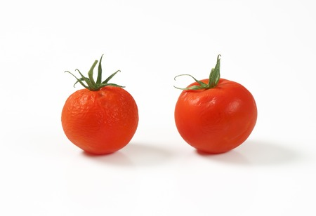 shrinking: two tomatoes going bad, on white background