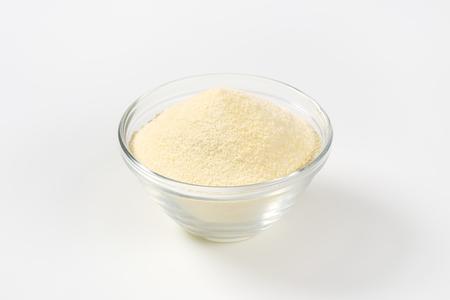 glass bowl: Heap of semolina flour in a glass bowl Stock Photo