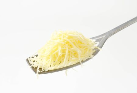 slotted: Heap of grated cheese on a slotted spatula